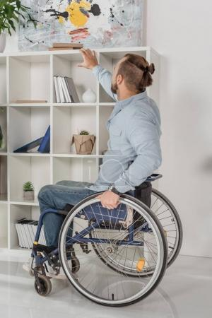 man on wheelchair trying to reach for book