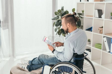 Photo for Handsome disabled man on wheelchair using digital tablet with instagram web page - Royalty Free Image