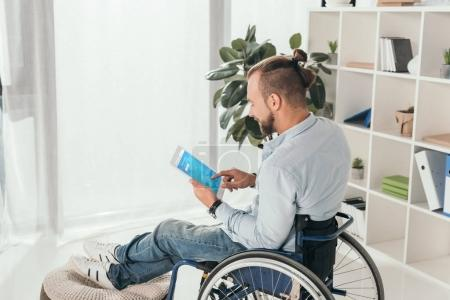 man on wheelchair using tablet