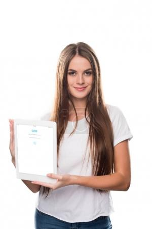 Girl holding tablet with Skype page