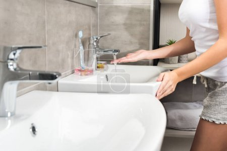 Girl putting hand under water