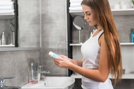 woman reading lotion description