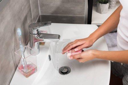 Photo pour Cropped image de jeune fille, se laver les mains avec du savon dans une salle de bain - image libre de droit