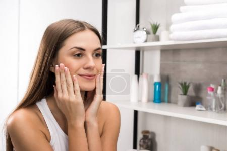Photo for Beautiful girl with clear skin applying cream on face - Royalty Free Image