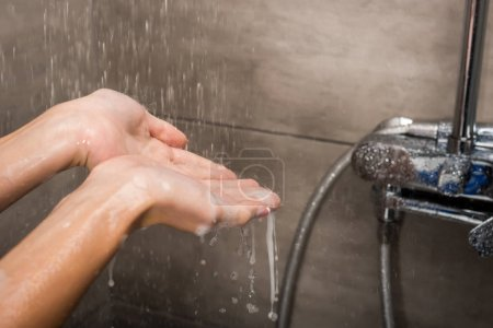 Photo for Cropped image of water drops falling on female hands in the shower - Royalty Free Image