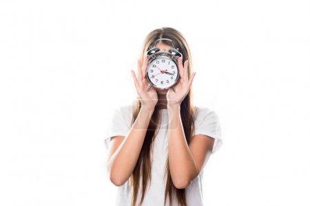Photo pour Jeune fille couvrant le visage avec réveil isolé sur blanc - image libre de droit