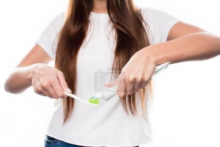 girl squeezing toothpaste on brush