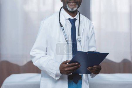 milieu médecin âgé avec le presse-papier