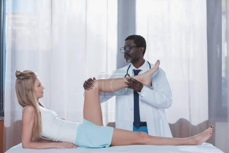 Photo pour Afro-américaine médecin examinant féminin genou patient alors qu'elle a couché sur une table médicale - image libre de droit