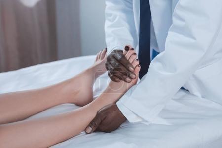 médecin examinant cheville du patient