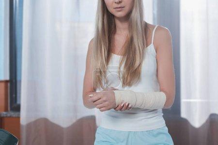 Foto de Recortar imagen de la chica con la mano lesionada en la clínica - Imagen libre de derechos