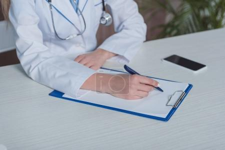 doctor writing something on clipboard