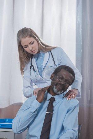 Photo pour Médecin examinant le cou d'un patient afro-américain à la clinique - image libre de droit