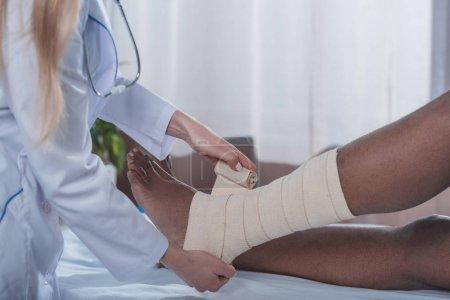Foto de Recortar imagen de médico vendaje la paciente afroamericana de la pierna - Imagen libre de derechos