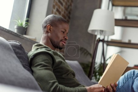 Photo for Side view of young african american man reading book at home - Royalty Free Image