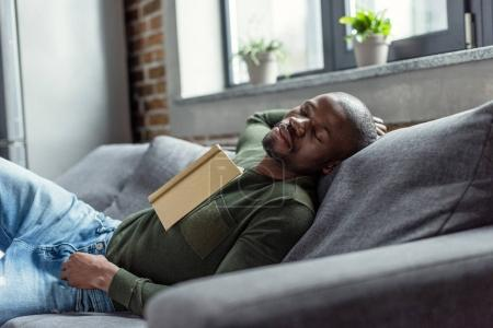Photo for Portrait of young african american man with book sleeping on sofa at home - Royalty Free Image