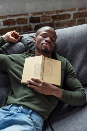 Photo pour Portrait de jeune homme afro-américain avec livre dormant sur canapé à la maison - image libre de droit