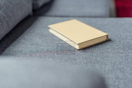 Photo pour Vue rapprochée du livre couché sur un canapé gris - image libre de droit