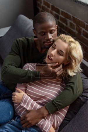 high angle view of sensual african american man hugging girlfriend while resting on sofa together