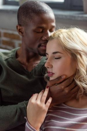 portrait of tender multicultural couple with eyes closed at home