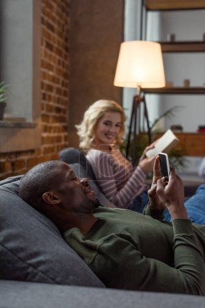 selective focus of african american man using smartphone while caucasian girlfriend reading book on sofa at home