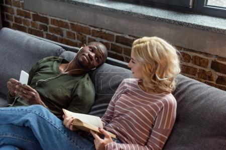 african american man listening music while caucasian girlfriend reading book on sofa at home