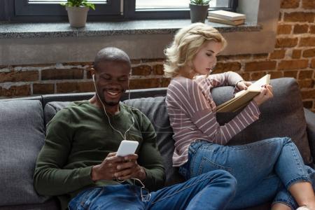 sourire de musique écoute afro-américain tout livre de lecture caucasien copine sur le canapé à la maison