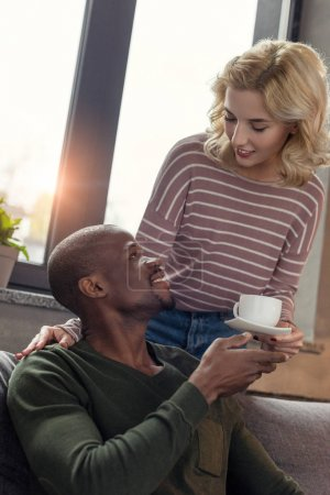 portrait of woman brought cup of coffee to smiling african american boyfriend