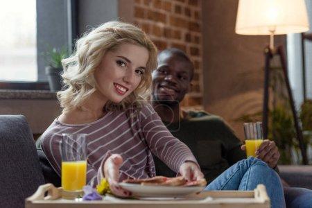Photo pour Mise au point sélective du sourire multiculturel jeune couple prenant le petit déjeuner ensemble à la maison - image libre de droit