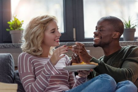portrait of happy multicultural young couple having breakfast together at home