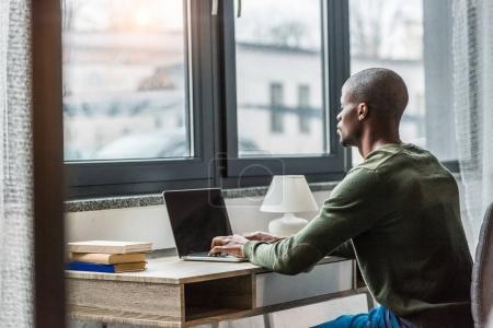 Photo pour Vue latérale de l'homme afro-américain tapant sur ordinateur portable tout en travaillant à la maison - image libre de droit