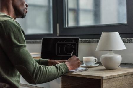 Photo pour Vue partielle de l'afro-américain de prendre des notes dans l'ordinateur portable tout en travaillant à la maison - image libre de droit