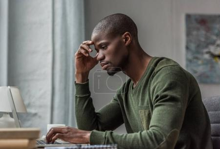 Photo for Pensive african american man using laptop while working at home - Royalty Free Image