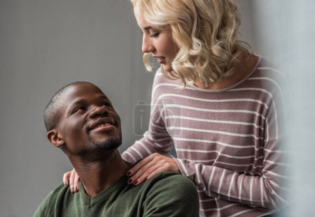 Photo for Portrait of young multiethnic couple looking at each other at home - Royalty Free Image