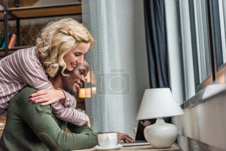 side view of smiling girlfriend hugging african american boyfriend that working on laptop at home