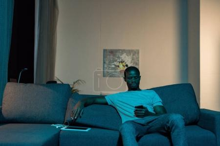 african american man with smartphone at home
