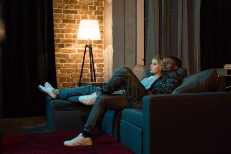side view of young multicultural couple watching tv together at home