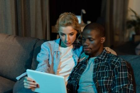 portrait of focused multicultural couple using tablet together while resting on sofa at home