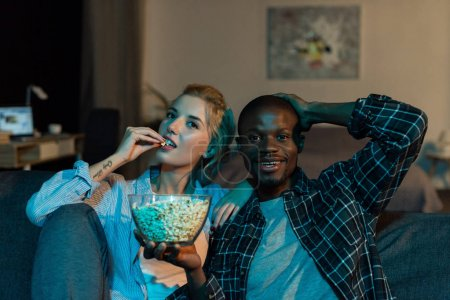 portrait of multiethnic couple eating popcorn and watching film together on sofa at home