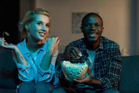 portrait of cheerful multiethnic couple watching tv together on sofa at home
