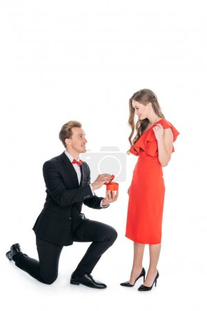 Photo for Young man standing on knees and proposing to happy woman isolated on white - Royalty Free Image