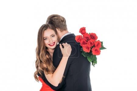 Photo pour Belle jeune femme heureuse souriant à la caméra tout en tenant bouquet de roses et étreignant petit ami isolé sur blanc - image libre de droit