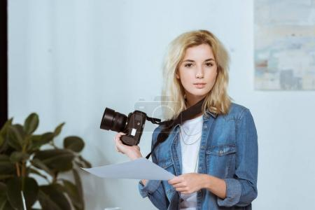 portrait of young photographer with photo camera and photoshoot example looking at camera in studio