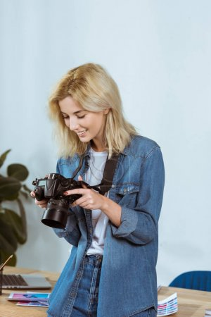 portrait of cheerful photographer looking at photo camera screen in hands in studio