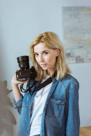portrait of smiling photographer with photo camera in hand looking at camera in studio