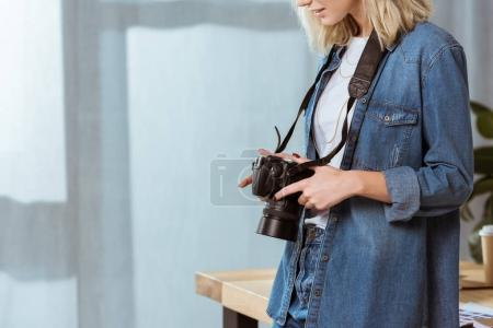 partial view of photographer with photo camera in hands in studio