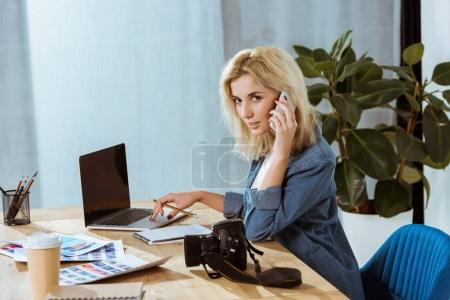 side view of young photographer talking on smartphone and looking at camera at workplace with laptop in studio