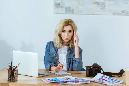 portrait of young photographer talking on smartphone while sitting at workplace in studio