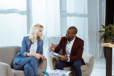 interracial photographers having discussion while choosing photos together in office