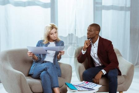 Foto de Fotógrafos interraciales elegir fotos juntos mientras estaba sentado en sillones de oficina - Imagen libre de derechos